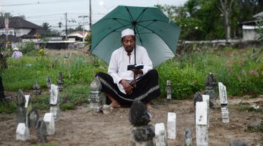 Seorang pria memanjatkan doa di makam kerabatnya saat Idul Fitri di Provinsi Narathiwat, Thailand, Rabu (5/6/2019). Tradisi ziarah kubur saat Idul Fitri ini mirip dengan apa yang biasa dilakukan muslim di Indonesia. (MADAREE TOHLALA/AFP)