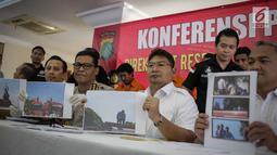 Kabid Humas Polda Metro Jaya Kombes Argo Yuwono didampingi jajaran menunjukkan foto kepada wartawan saat rilis pengungkapan tindak pidana perampasan truk tangki Pertamina di Polda Metro Jaya, Jakarta, Selasa (19/3). (Liputan6.com/Faizal Fanani)
