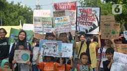 Aktivis lingkungan hidup dari berbagai LSM membawa spanduk bertuliskan pesan saat berjalan kaki menuju Taman Aspirasi di Istana Merdeka, Jakarta, Jumat (29/11/2019). Aktivis meminta pemerintah segera mendeklarasikan perubahan iklim yang semakin kritis. (merdeka.com/Imam Buhori)