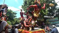 Para pekerja menaruh patung atau yang dikenal ogoh-ogoh diatas mobil untuk dibawa jelang Perayaan Nyepi di Denpasar, Bali (12/3). Dalam perwujudannya ogoh-ogoh digambarkan sebagai sosok yang besar dan menakutkan. (AFP Photo/Sonny Tumbelaka)