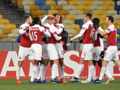 Pemain Arsenal merayakan gol pembuka yang dicetak oleh pemain muda, Emile Smith Rowe ke gawang Vorskla pada laga lanjutan Grup E Liga Europa yang berlangsung stadion NSK Olimpiyskiy, Kyiv, Jumat (30/11). Arsenal menang atas Vorskla 3-0. (AFP/Sergei Supins