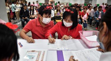 Sepasang suami istri mendaftarkan surat nikah mereka pada Hari Valentine di Bang Rak atau Distrik Cinta di Bangkok, Thailand, Jumat (14/2/2020). Banyak pasangan menikah di Distrik Cinta karena mereka percaya akan membawa keberuntungan dan cinta yang tahan lama. (Lillian SUWANRUMPHA/AFP)
