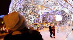 Pengunjung berfoto dekat bola natal raksasa di Octyabrskaya Square dan dekorasi untuk menyambut perayaan Natal 2018 dan Tahun Baru 2019 di Minsk, Belarus, Selasa (18/12). (AP Photo/Sergei Grits)
