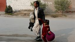 Seorang pria membawa kedua anaknya untuk menyalmatkan diri saat terjadi serangan di dekat kantor amal Inggris Save the Children di Jalalabad, Afghanistan (24/1). (AFP Photo/Noorullah Shirzada)