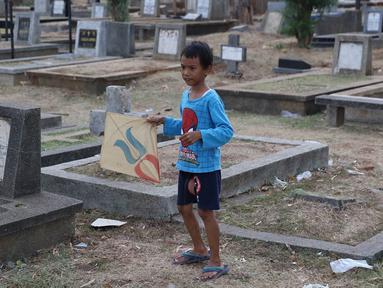 Seorang anak bermain layangan di TPU Menteng Pulo, Jakarta, Kamis (18/10). Padatnya pemukiman penduduk serta gedung bertingkat di kawasan tersebut menyebabkan anak-anak terpaksa bermain di tempat yang tidak semestinya. (Liputan6.com/Immanuel Antonius)