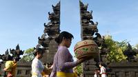 Sejumlah wanita Hindu membawa sesajen menuju pura untuk sembahyang Hari Raya Galungan di Jimbaran, Bali, Rabu (5/4). Galungan dirayakan oleh umat hindu di Bali sebagai hari kemenangan Dharma (Kebaikan) melawan Adharma (Keburukan). (SONNY TUMBELAKA/AFP)