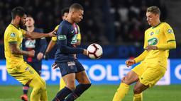 Striker PSG, Kylian Mbappe, berusaha melewati para pemain Nantes pada laga Piala Prancis di Stadion Parc des Princes, Paris, Rabu (3/4). Mbappe dinobatkan jadi pemain terbaik Liga Prancis. (AFP/Anne Christine Poujoulat)