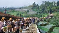 Warga membawa tenongan menuju makam sesepuh mereka saat mengikuti Sadranan Rejeban Plabengan di Lereng Gunung Sumbing, Temanggung, Jawa Tengah, Jumat (22/3). Dalam tradisi ini warga menggelar doa dan makan bersama di makam sesepuh. (Liputan6.com/Gholib)