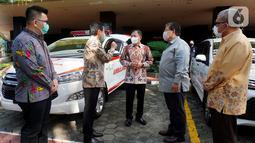Menkes TerawanAgus Putranto (tengah) berbincang dengan jajaran Direksi PT Toyota Astra Motor (TAM) pada acara penyerahan bantuan untuk penanganan Covid-19 di Jakarta Rabu (20/5/2020). TAM dan SERA juga memberikan bantuan 3 mobil ambulan Kijang Innova dan 48 Toyota Avanza. (Liputan6.com/HO/Ady)