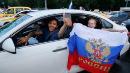 Suporter Rusia berpesta merayakan keberhasilan negaranya mengalahkan Spanyol pada laga 16 besar Piala Dunia di Moskow, Minggu (1/7/2018). Rusia untuk pertama kalinya lolos ke babak perempatfinal. (AFP/Maxim Zmeyev)