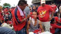 Pelukis wajah menggunakan duel Malaysia dan Timnas Indonesia U-22 di SEA Games sebagai ajang cari keuntungan. (Liputan6.com/Cakrayuri Nuralam)