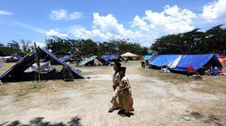 Anak-anak pengungsi berjalan di kamp pengungsian di Lapangan Masjid Agung Daru Salam, Palu, Jumat (5/10). Para pengungsi menggelar salat jumat pertama pascagempa bumi dan tsunami. (Liputan6.com/Fery Pradolo)