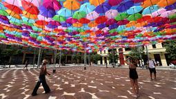 Pengunjung melewati instalasi Umbrella Sky Project di Aix-en-Provence, Prancis, Jumat (28/6/2019). Spot berteduh yang instagramable tersebut merupakan karya seniman Portugis Patricia Cunha. (BORIS HORVAT/AFP)
