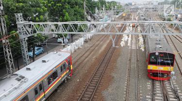 KRL melintas di jalur dwiganda atau double-double track (DDT) kawasan Jatinegara, Jakarta, Jumat (12/4). DDT segmen Jatinegara-Cakung mulai digunakan pada hari ini. (Liputan6.com/Herman Zakharia)