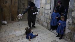 Seorang pria Yahudi ultraortodoks mengayunkan ayam di atas keluarganya saat melakukan ritual Kapparot di Yerusalem, 12 September 2021. Kapparot adalah ritual transfer dosa ke ayam yang dilakukan sebelum Yom Kippur (Hari Penebusan). (MENAHEM KAHANA/AFP)