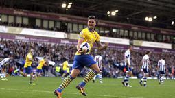 Striker Arsenal Olivier Giroud merlakukan selebrasi setelah rekan setimnya Jack Wilshere berhasil menjebol gawang West Bromwich Albion (06/10/2013). (AFP