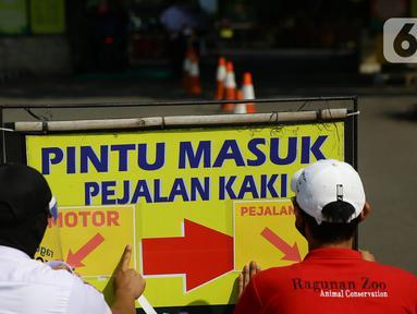 Petugas memasang penunjuk akses masuk pengunjung di Taman Margasatwa Ragunan, Jakarta, Sabtu (20/6/2020). Ragunan mulai dibuka kembali untuk pengunjung pada Sabtu ini di masa PSBB transisi dengan pembatasan dan penerapan protokol kesehatan yang ketat. (Liputan6.com/Herman Zakharia)