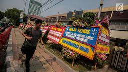 Warga melintasi karangan bunga di Halaman Polres Jakarta Barat, Jumat (23/11). Puluhan karangan bunga yang dikirimkan warga tersebut diberikan guna mendukung pihak kepolisian dalam memberantas aksi premanisme di Jakarta Barat. (Liputan6.com/Faizal Fanani)