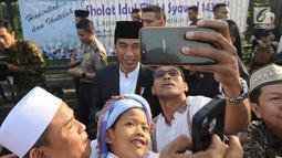 Seorang warga berselfie dengan Presiden Joko Widodo usai melaksanakan salat id Hari Raya Idul Fitri 1 Syawal 1439 H di Lapangan Astrid, Kebun Raya Bogor, Jumat (15/6). (Merdeka.com/Arie Basuki)