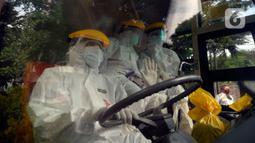 Petugas Dishub memakai baju APD akan menjemput korban yang diduga terjangkit Covid-19 menggunakan bus sekolah di Puskesmas Kebayuran Lama, Jakarta, Senin (6/7/2020). Bus sekolah tersebut selama liburan dibantukan untuk mengangkut pasien Covid-19 ke Wisma Atlet Kemayoran. (merdeka.com/Dwi Narwoko)