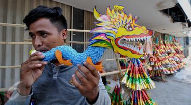 Pengrajin terompet mencoba terompet buatannya di kawasan Kota Tua, Jakarta (26/12/2015). Para pengrajin ini datang dari Sukatani di Bekasi untuk mencoba peruntungan menjual terompet di Jakarta. (Liputan6.com/Gempur M Surya)