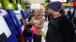 Petugas frontliner membantu calon penumpang membeli tiket di Stasiun Gambir, Jakarta, Minggu (21/4). PT KAI Daop 1 Jakarta mewajibkan petugas frontliner wanita dan pria mengenakan kebaya dan batik untuk menyambut Hari Kartini. (Liputan6.com/Johan Tallo)