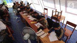 Murid SMP dan SMA Sekolah Khusus (SKh) Assalam 01 melaksanakan ujian di tenda darurat halaman SKh Assalam 02, Ciater, Serpong, Tangerang Selatan, Selasa (3/12/2019). Mereka terpaksa melaksanakan ujian dalam tenda lantaran gedung sekolahnya ambruk akibat pergerakan tanah. (merdeka.com/Arie Basuki)