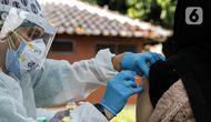 Vaksinator menyuntikkan vaksin COVID-19 kepada warga saat vaksinasi keliling di Kebon Kacang, Jakarta, Jumat (9/7/2021). Mobil vaksin COVID-19 keliling diluncurkan guna mempercepat pencapaian target vaksinasi COVID-19 untuk mencapai kekebalan kelompok atau herd immunity. (Liputan6.com/Faizal Fanani)