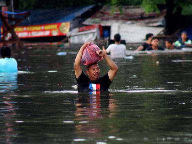 Warga melintasi banjir yang merendam perumahan Villa Mutiara Pluit, Tangerang, Banten, Senin (3/2/2020). Banjir disebabkan jebolnya tanggul sungai di sekitar kawasan tersebut. (merdeka.com/Magang/Muhammad Fayyadh)