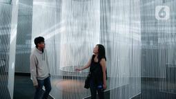Pengunjung berpose saat mengunjungi pameran seni berbasis teknologi berwujud sorotan cahaya futuristik 'Wave of Tomorrow' di Jakarta, Sabtu (21/12/2019). Pameran seni Wave of Tomorrow menghadirkan tiga kelompok instalasi yaitu legacy, now, dan tomorrow.  (Liputan6.com/Faizal Fanani)