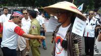 Cak Tatang namanya. Dia berdiri di halaman gedung Mahkamah Konstitusi (MK), Jakarta dengan topi caping ala petani. (Ahmad Romadoni/Liputan6.com)