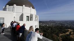 Wisatawan melihat pemandangan Kota Los Angeles dari puncak bangunan Griffith Observatory & Planetarium, California (14/3/2016). (Reuters/ Mario Anzuoni)