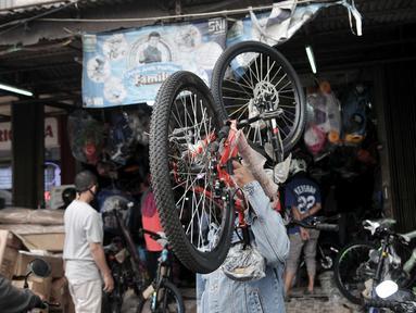 Warga memikul sepeda yang baru dibeli di sebuah toko di Kramat Jati, Jakarta, Minggu (21/6/2020). Dalam sebulan terakhir, penjualan sepeda di Ibu Kota meningkat hingga 50 persen seiring minat dan tren warga yang melonjak menggunakan transportasi gowes itu di masa pandemi. (merdeka.com/Iqbal Nugroho)