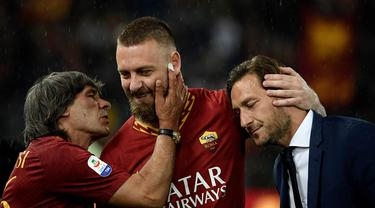 Gelandang AS Roma, Daniele De Rossi, bersama Bruno Conti dan Francesco Totti usai melawan Parma pada laga Serie A di Stadion Olympic, Roma, Minggu (26/5). Laga ini perpisahan bagi De Rossi dan AS Roma setelah 18 tahun. (AFP/Filippo Monteforte)