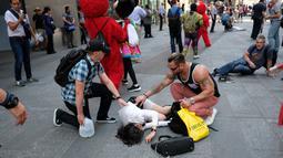 Sejumlah orang menghampiri korban terluka setelah sebuah mobil melaju kencang ke arah pejalan kaki di trotoar Times Square, New York, Kamis (18/5). Pihak berwenang menyebut tidak ada indikasi tindakan terorisme terkait kejadian itu. (Jewel SAMAD/AFP)