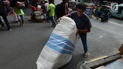 Pekerja membawa barang dagangan di Pasar Tanah Abang, Jakarta, Sabtu (25/5/2019). Pasca Aksi 22 Mei 2019, para pedagang mengalami kerugian karena perputaran uang di Tanah Abang mencapai Rp 200 miliar per hari. (merdeka.com/Imam Buhori)