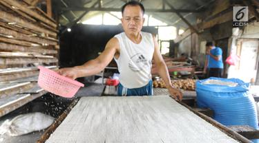 Pengrajin melakukan proses pembuatan tahu di kawasan Sukaraja, Bogor, Kamis (6/9). Naiknya harga kedelai impor akibat melemahnya nilai tukar rupiah terhadap dolar AS membuat pengrajin mengurangi ukuran dan takaran pembuatan tahu. (Merdeka.com/Arie Basuki)