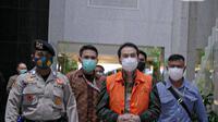 Wakil Ketua DPR Aziz Syamsuddin digiring petugas menuju mobil tahanan di Gedung KPK Jakarta, Sabtu (25/9/2021). Politisi Partai Golkar ini ditetapkan sebagai tersangka dan langsung ditahan KPK terkait kasus penanganan perkara di Kabupaten Lampung Tengah. (Liputan6.com/Faizal Fana