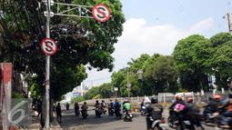 Pengendara melintas di bawah rambu larangan berhenti di Jalan Mampang Prapatan, Jakarta, Jumat (12/8). Pemprov DKI Jakarta secara bertahap akan mengganti rambu larangan parkir dan berhenti yang digunakan saat ini. (Liputan6.com/Helmi Fithriansyah)