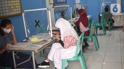 Sejumlah siswa mengikuti PJJ di Balai Warga RT 05/RW 02 Kelurahan Galur, Johar Baru, Jakarta, Selasa (15/8/2020). Program Internet Gratis untuk semua yang digalakan Pemprov DKI Jakarta ditujukan untuk mengatasi persoalan kesenjangan digital selama pandemi Covid-19. (Liputan6.com/Fery Pradolo)