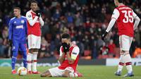 Penyerang Arsenal, Pierre-Emerick Aubameyang (tengah) menutup wajahnya usai pertandingan melawan Olympiakos pada leg kedua babak 32 besar Liga Europa di stadion Emirates, London, Kamis (27/2/2020).  Olympiakos menang 2-1 dan lolos dengan unggul agregat gol tandang 2-2. (AP Photo/Frank Augstein)