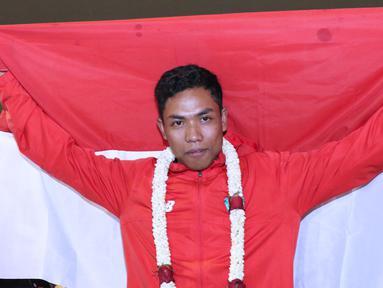 Pelari muda Indonesia, Lalu Muhammad Zohri membentangkan bendera Merah Putih saat penyambutan di Terminal 3 Bandara Soetta, Tangerang, Selasa (17/7). Lalu M Zohri meraih emas lari 100m putra di Kejuaraan Dunia U-20 IAAF. (Liputan6.com/Helmi Fithriansyah)