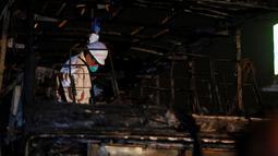 Seorang petugas memeriksa kerangka  sebuah bus bertingkat yang hangus terbakar di terminal bus antarprovinsi, kota Lima, Peru, Minggu (31/3). Para korban kebanyakan berada di lantai 2, mereka terjebak tidak bisa turun menyelamatkan diri. (REUTERS/Stringer)