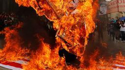 Para pengunjuk rasa membakar patung karakter Presiden AS Donald Trump saat melakukan aksi protes pada peringatan Hari Buruh di Bogota, Kolombia (1/5). Mereka melakukan aksi dengan membakar patung Donald Trump. (AP/Fernando Vergara)