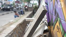 Kondisi tembok Jalan Juanda yang ambruk di kawasan Depok, Jawa Barat, Senin (2/12/2019). Kondisi tembok yang dipenuhi mural tersebut mulai rapuh dan sebagian sisinya telah ambruk serta miring sehingga membahayakan pejalan kaki. (Liputan6.com/Immanuel Antonius)
