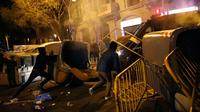 Demonstran pro kemerdekaan Catalonia merusak tempat sampah dan besi pembatas di Barcelona, Spanyol, Minggu (25/3). Demonstran memprotes penangkapan mantan pemimpin ekstrem Catalonia, Carles Puigdemont. (Foto AP/Emilio Morenatti)