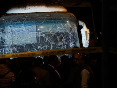 Pasukan keamanan berdiri di dekat sebuah bus wisata setelah serangan bom pinggir jalan di sebuah daerah dekat Piramida Giza di Kairo, Mesir (28/12). Insiden tersebut menewaskan  dua turis Vietnam dan 12 lainnya terluka. (AP Photo/Nariman El-Mofty)