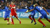 Gelandang Wales, Aaron Ramsey, berusaha melewati pemain Prancis pada laga persahabatan di Stadion Stade de France, Sabtu (11/11/2017). Prancis menang 2-0 atas Wales. (AP/Francois Mori)