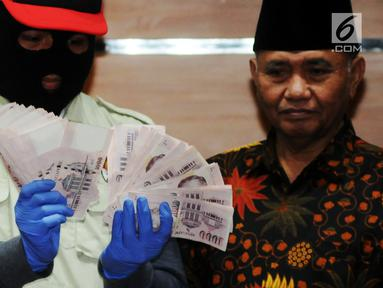 Pimpinan KPK, Agus Rahardjo (kanan) bersama Penyidik menunjukan barang bukti Oprasi Tangkap Tangan (OTT) uang 130.000 Dollar Singapore atau setara Rp 1,3 milyar di gedung KPK, Jakarta, Rabu (29/8). (merdeka.com/Dwi Narwoko)