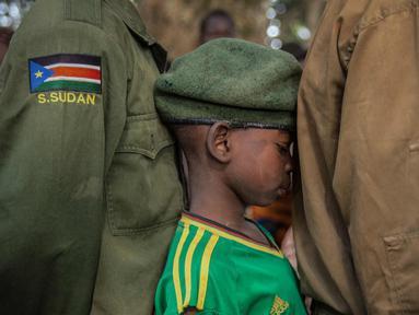 Seorang tentara anak yang baru dibebaskan menunggu dalam antrean di Yambio, Sudan Selatan, (7/2). Sebanyak 311 tentara anak-anak, termasuk 87 anak perempuan, telah dibebaskan oleh kelompok bersenjata di Sudan Selatan. (AFP PHOTO/Stefanie Glinski)